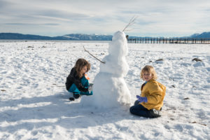Kids building a snowman on the Tahoe beach